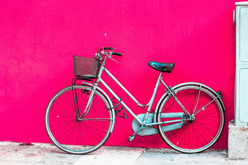 Bicycle standing near bright pink wall.