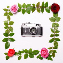 Flat lay - Retro photo camera and rose leaves and roses around i