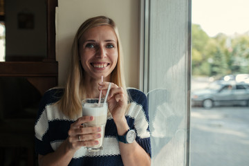 Portrait of young woman drinks coffee latte in cafe near the window