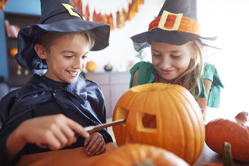 Elementary age sibling drilling in pumpkin