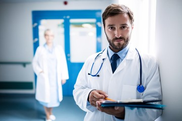 Confident doctor with clipboard standing in hospital corridor