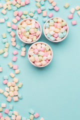 Colorful Candy Background. Small colored Marshmallows on blue table. Top view, celebration concept, copy space for text