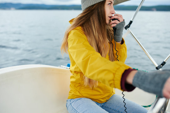 Young woman talking on the radio on the sailboat