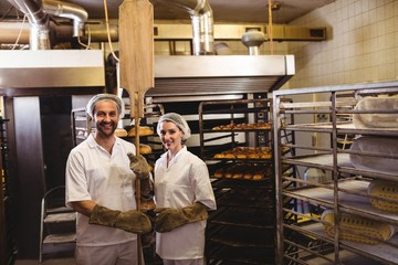 Portrait of female and male baker standing together