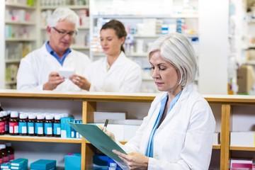 Pharmacist writing on clipboard