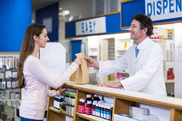 Pharmacist giving medicine package to customer