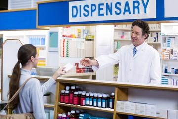 Pharmacist giving medicine box to customer