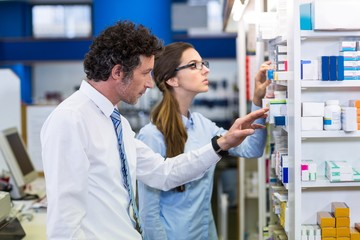 Pharmacists checking medicines on shelf in pharmacy