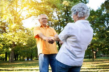 Senior couple having fun and dance in the park