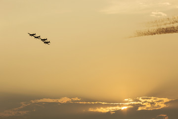 Silhouette of four formation of airplanes at sunset
