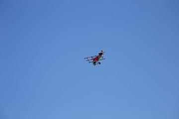 Red WWI Fokker Triplane in Flight on clear blue Sky