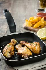 Roast chicken drumsticks on a fried pan