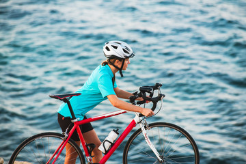 Female cyclist standing on a rock and looking at sea