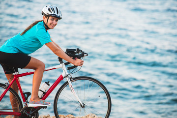 Female cyclist riding bike with sea on background