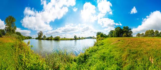 Wall Mural - Landschaft mit Fluss, Wiesen, blauen Himmel und Sonne