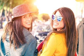 Young women walking on the street turning back and smiling - Cheerful girlfriends carefree attitude looking at camera outdoors with day light and car background - Concept of friendship and leisure