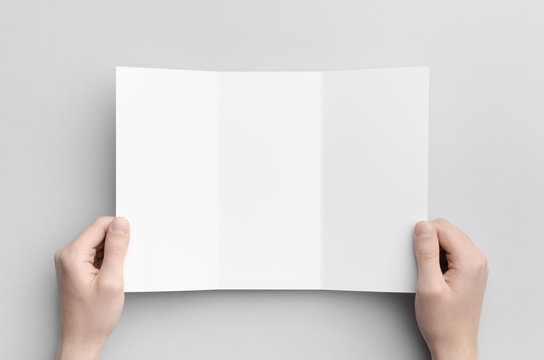A4 Tri-Fold Brochure Mock-Up - Male hands holding a blank tri-fold on a gray background.