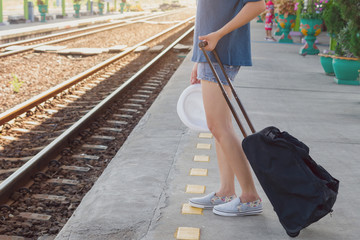 beautiful woman carrying her bag and hat waiting for a train at a railway station,vacation concept