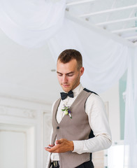The groom looks at his watch.