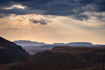Dramatic sky, storm clouds and sun rays glowing over valleys, canyons and table mountains of the majestic Golden Gate Highlands National Park, South Africa.