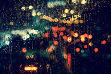 City view through a window on a rainy night,Rain drops on window with road light bokeh, City life in night in rainy season abstract background. Wall mural