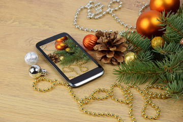 Smartphone and Christmas tree on wooden background. Christmas gr