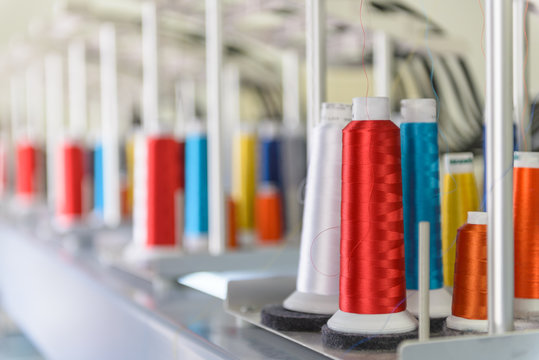 Colorful spools of thread on an industrial sewing machine.