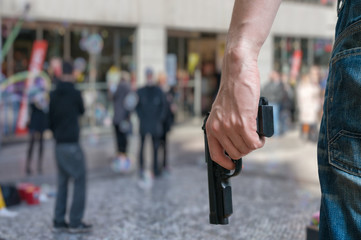 Armed man (attacker) holds pistol in public place. Many people on street. Gun control concept.
