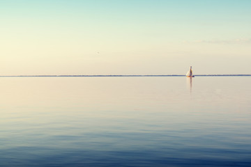 Water landscape with white sailing boat on calm waters in the light of the sunset. Toned and processing photos.