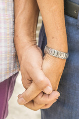 Closeup of loving couple holding hands while walking