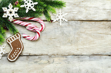 wood background with Christmas tree, candy, cookies, and snowfla