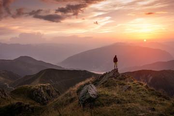 Fotorolgordijn Chocoladebruin Man standing on a mountain summit at sunset