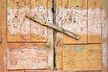Abandoned broken wooden shed door and lock. scored window