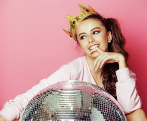 young cute disco girl on pink background with disco ball and crown