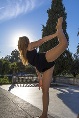 Beautiful ballerina doing exercises for dancing outdoors
