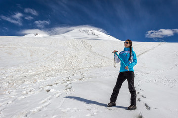 Beautiful smiling mountaineer woman with ice axe, sunglasses and Elbrus mountain summits on background. Active lifestyle, freedom, success concept