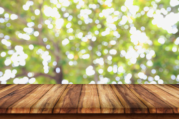 Empty wooden table with bokeh abstract green background.