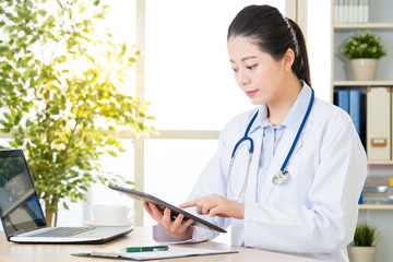 doctor using digital tablet to research patient's medical case