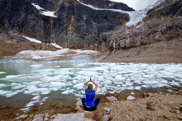 Woman relaxing and meditaing in lotus pose by lake. Angel Glacier at Mount Edith Cavell. Jasper National Park. Canadian Rockies. Alberta. Canada.