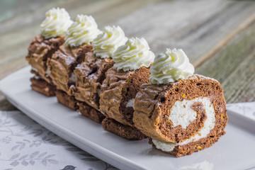 Five pieces Chocolate roll filled with whipped cream on white tr