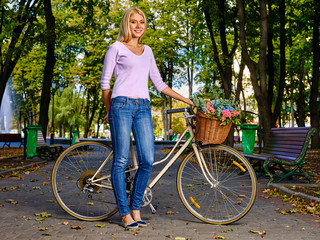 Beautiful young woman on bicycle in park outdoor. Woman ride flowers on bicycle in autumn park.