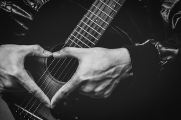 music lover, male hand sign on acoustic guitar. bw filter