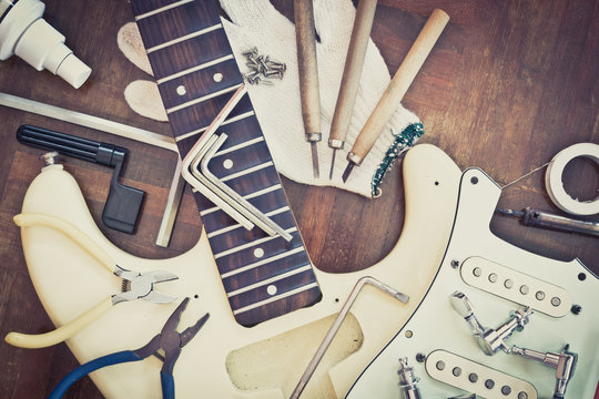 yellow electric guitar on wood in repair & luthier workshop, fixing & musical instrument repairing concept