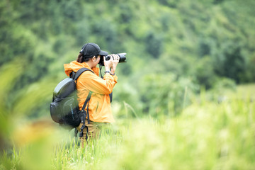 Professional woman photographer taking outdoor portraits with prime lens