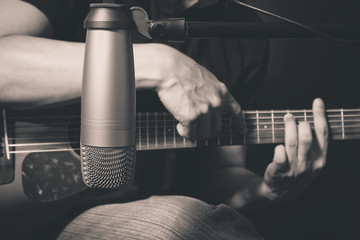 male musician playing acoustic guitar behind condenser microphone in recording studio, bw film filter
