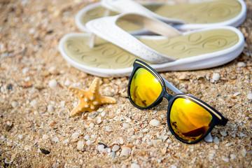 White flip flops, sun glasses and starfish on white sandy beach.