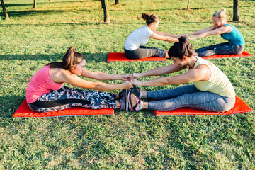 Women doing stretching exercises in pairs
