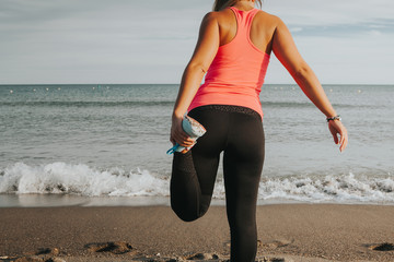 Stretching legs and quadriceps before running workout at the beach. Woman back view.