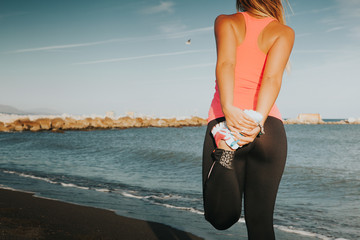 Stretching legs and quadriceps before running workout at the beach. Woman back.