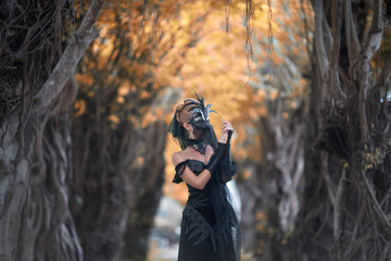 Woman in mysterious place,creative mask and long black dress create dramatic atmosphere